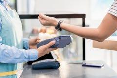 支付由NFC的无法认出的妇女 库存照片