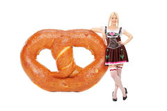 支持一个巨大的椒盐脆饼的德国女孩 免版税图库摄影