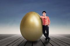支持一个巨大的金黄鸡蛋的商人 免版税图库摄影
