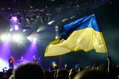 支持一个执行的乌克兰摇滚乐队的乌克兰旗子 免版税库存图片