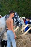 支持一个白马的一个年轻人的画象 免版税库存照片