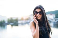 支持一条河的黑礼服的美女在布拉格,打电话 免版税图库摄影