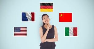 支持各种各样的旗子的体贴的女实业家反对蓝色背景 库存图片