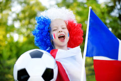 支持和欢呼她的国家橄榄球队的滑稽的小女孩 图库摄影