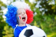 支持和欢呼她的国家橄榄球队的滑稽的小女孩 库存图片