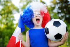 支持和欢呼她的国家橄榄球队的滑稽的小女孩 免版税图库摄影