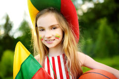 支持和欢呼她的国家蓝球队的滑稽的小女孩在篮球冠军期间 库存图片