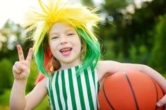 支持和欢呼她的国家蓝球队的滑稽的小女孩在篮球冠军期间 免版税库存照片