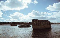 支持在河的被毁坏的桥梁反对蓝天 库存照片