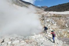 支持在火山口活火山的游人抽烟的喷气孔 免版税库存照片