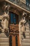 支持大厦大阳台在巴黎巴黎人样式的木门和雕塑以人的形式 库存照片