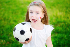 支持她的国家橄榄球队的可爱的小女孩在足球冠军期间 免版税库存图片