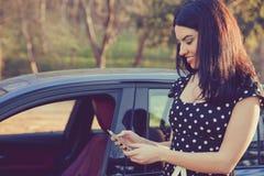 支持她的汽车的成功的少妇发短信在手机 库存照片