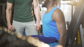 支持年轻人的朋友在健身房的困难的锻炼期间,给上流五 股票录像