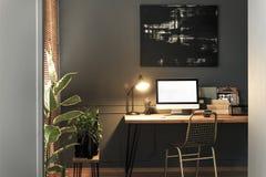 支持有灯的,笔记本的金椅子木书桌和 库存照片