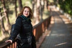 支持木篱芭的Atractive愉快的妇女在森林里, 免版税库存照片