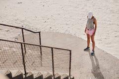 支持楼梯的少妇在海滩 图库摄影