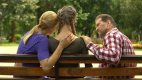 支持沮丧的女儿的慈爱的父母坐长凳在公园,悲伤 影视素材