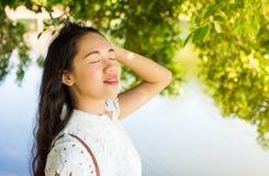 支持湖和享用夏天微风的女孩 库存照片