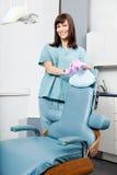 支持牙齿椅子的微笑的女性牙医在 图库摄影