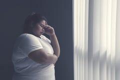 支持窗口的被注重的肥胖妇女 图库摄影