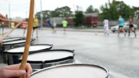 支持赛跑者的鼓手的慢动作在马拉松期间在下雨天 defocused赛跑者背景 股票视频