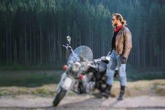 支持他定制的巡洋舰摩托车的骑自行车的人 免版税库存照片