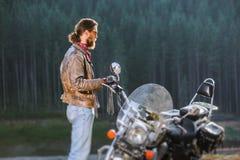 支持他定制的巡洋舰摩托车的骑自行车的人 图库摄影
