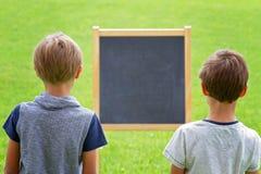 支持黑板的两个男孩户外 库存照片