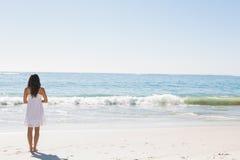 支持水的白色阳光服的浅黑肤色的男人 免版税图库摄影