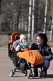 支架的小孩有母亲的在城市公园 库存照片
