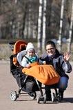 支架的小孩有母亲的在城市公园 库存图片