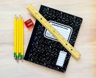 4支铅笔、一把铅笔刀、一个统治者和一个笔记本在一张木书桌上 库存图片