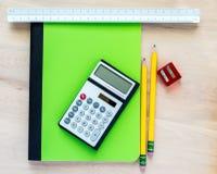 2支铅笔、一把铅笔刀、一个计算器、一个三角统治者和一个绿色笔记本在一张木书桌上 免版税库存图片