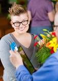 支付与信用卡的女性花店顾客 免版税库存照片