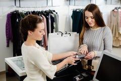 支付与信用卡的妇女在s陈列室里 免版税库存图片