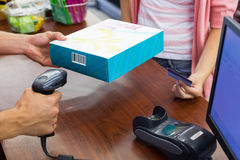 支付与信用卡的收款机的微笑的妇女和扫描一个产品 库存图片