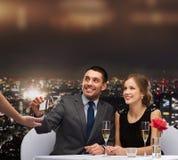 支付与信用卡的晚餐的微笑的夫妇 图库摄影