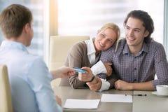 支付与卡片的年轻愉快的夫妇 免版税库存照片
