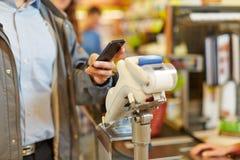 支付与智能手机的人在超级市场结算离开 库存图片