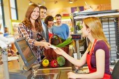 支付与EC卡片的妇女在超级市场结算离开 免版税库存图片