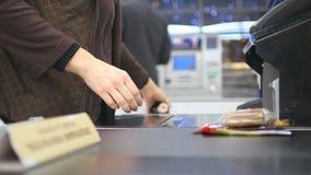 支付产品的顾客在结算离开 在传送带的食物在超级市场 有出纳员和终端的收银处 影视素材