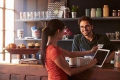 支付使用数字式片剂读者的咖啡店的顾客 免版税库存照片
