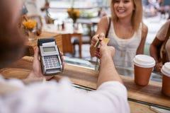 支付在与信用卡的一个咖啡馆的顾客 库存照片
