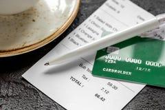 支付支票在咖啡馆的午餐与在黑暗的桌背景的信用卡 库存照片