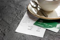 支付支票在咖啡馆的午餐与在黑暗的桌背景的信用卡 免版税图库摄影