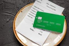 支付支票在咖啡馆的午餐与在黑暗的桌背景的信用卡 免版税库存图片