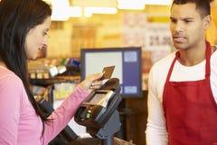 支付购物的顾客在与卡片的结算离开 免版税库存照片