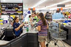 支付购物的顾客在超级市场 在现金的线 免版税库存照片