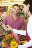 支付购物的顾客在超级市场结算离开 免版税库存图片